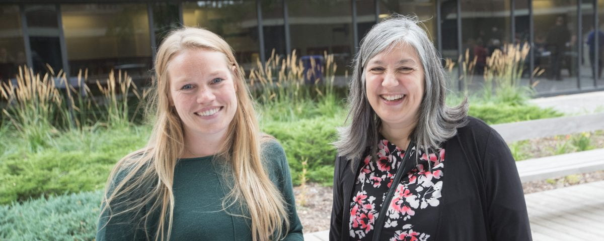 Two women on campus grounds smile at the camera