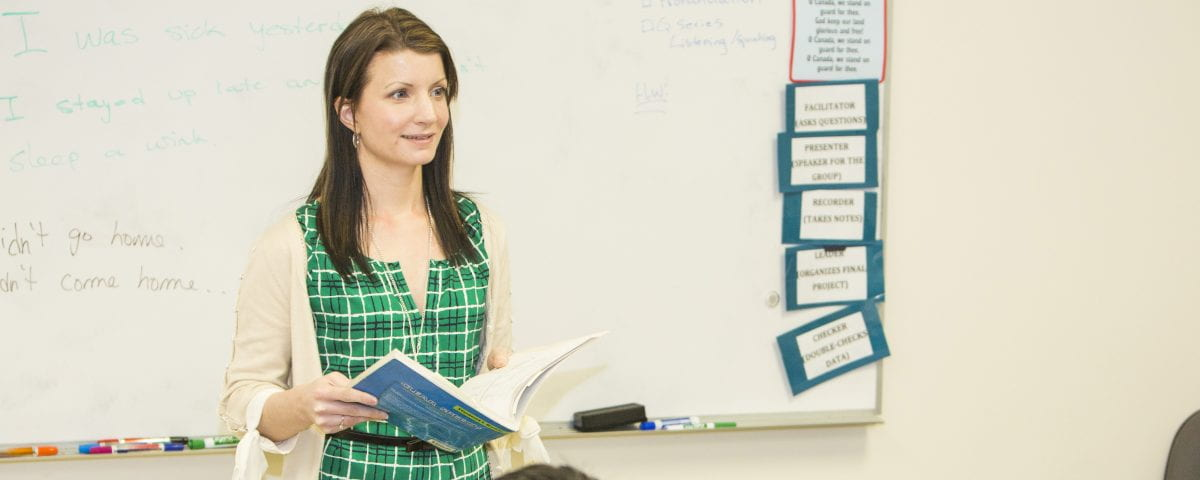 An instructor stands in front of a white board teaching to her class