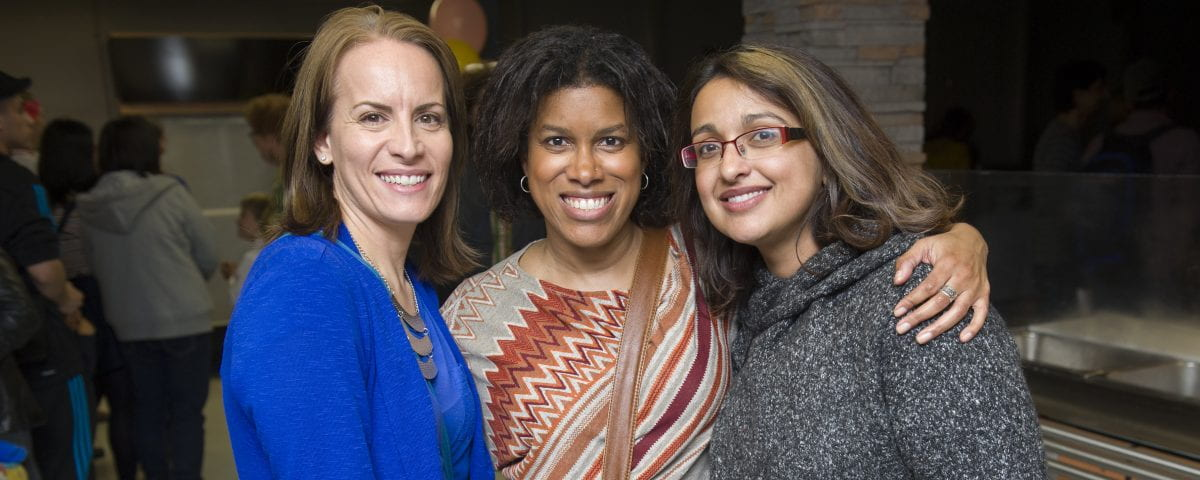 Three women are standing shoulder-to-shoulder while smiling