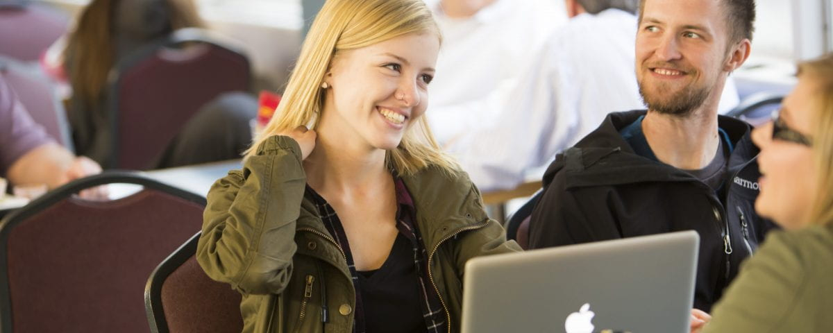 A woman smiles with her peers while seated in front of her laptop