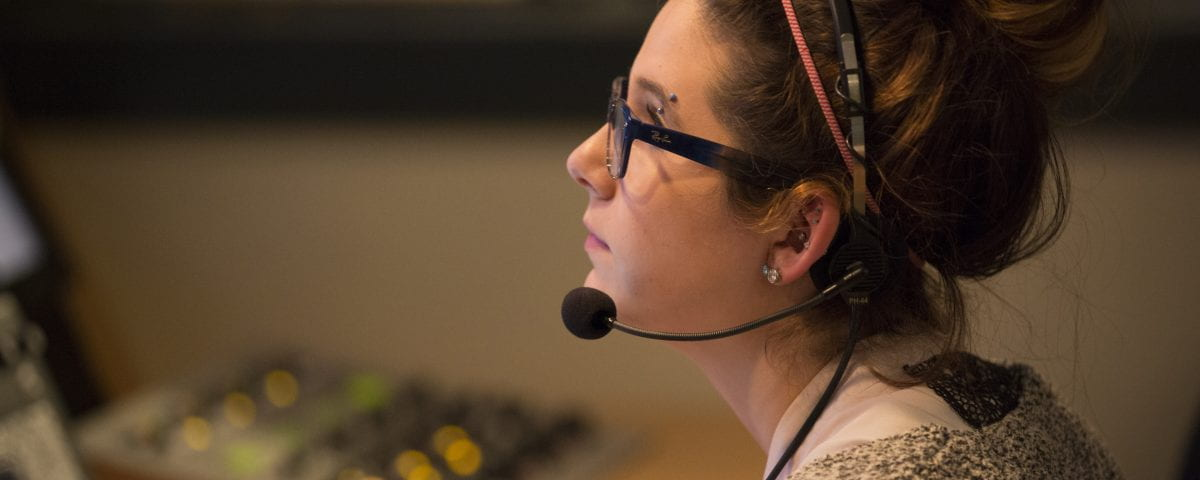 A woman sits in a media studio wearing a headset