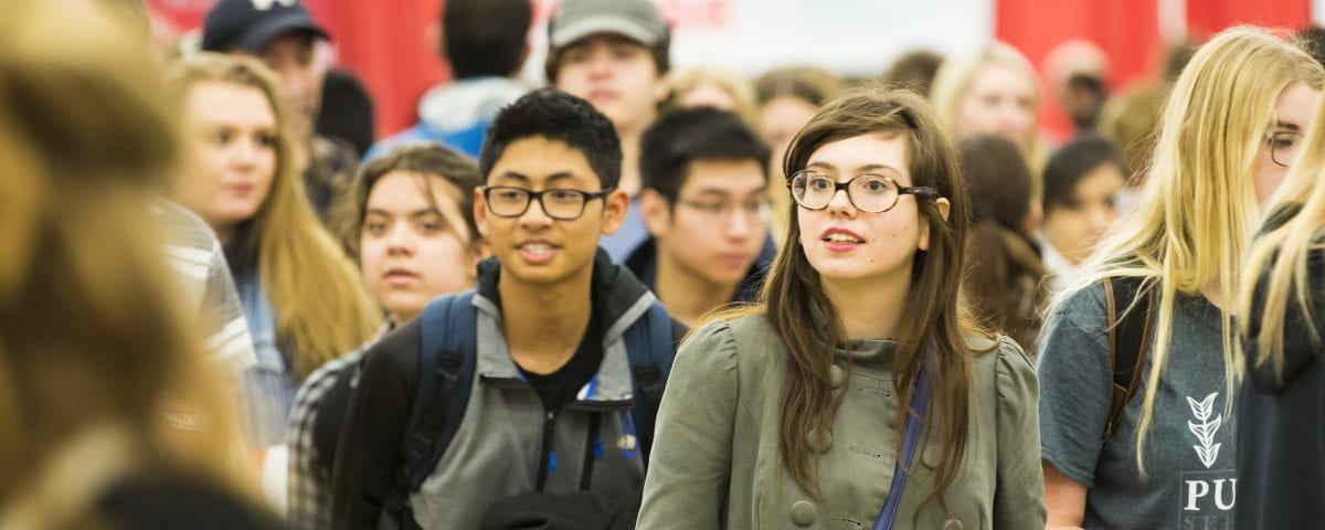 A hallway full of students are pictured looking around campus