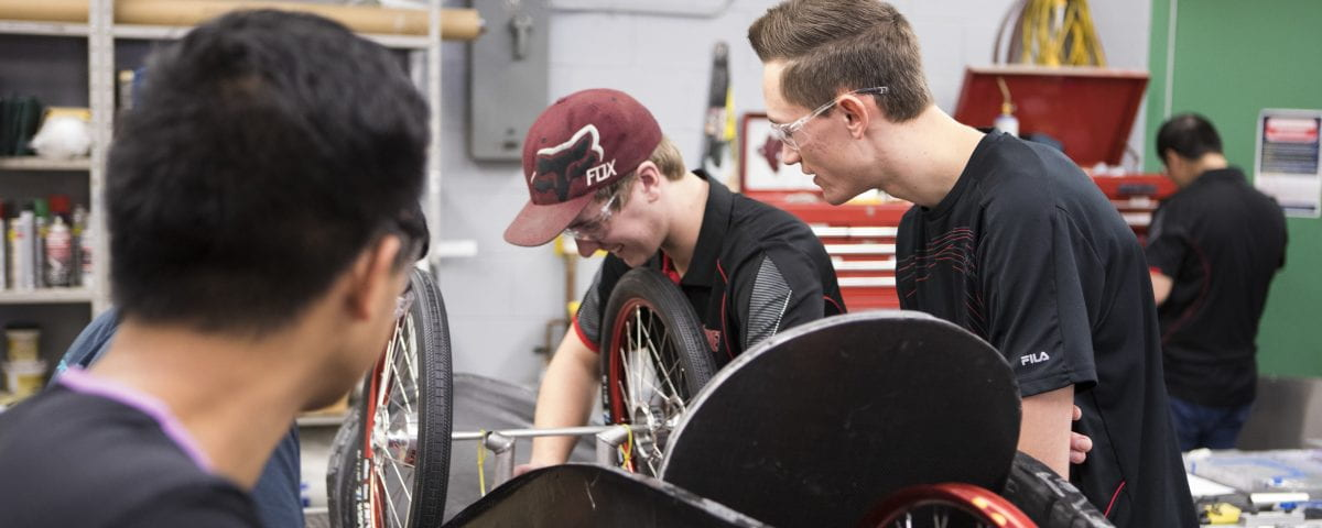 Two students build a bicycle in a lab