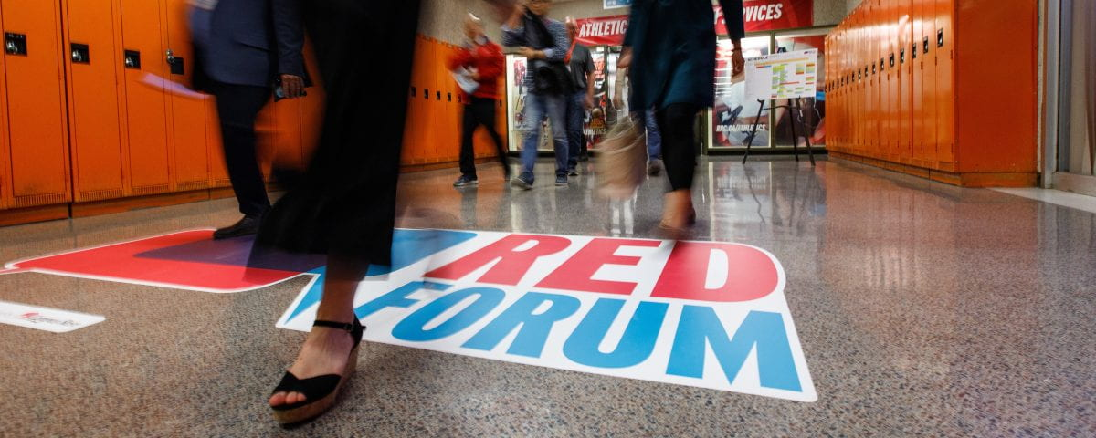 The RED Forum logo is pictured as people stroll the hallways to various sessions