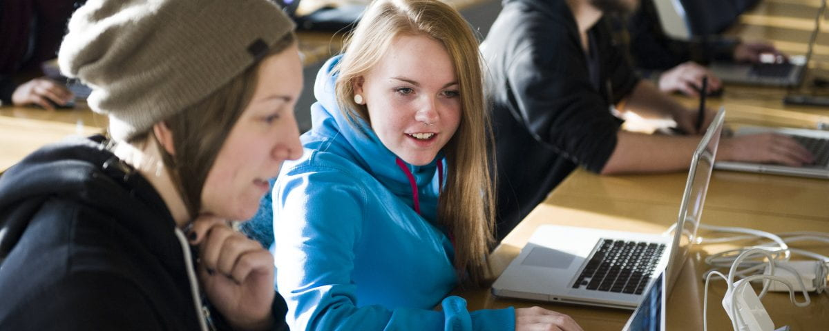Students are pictured interacting over coursework in the classroom