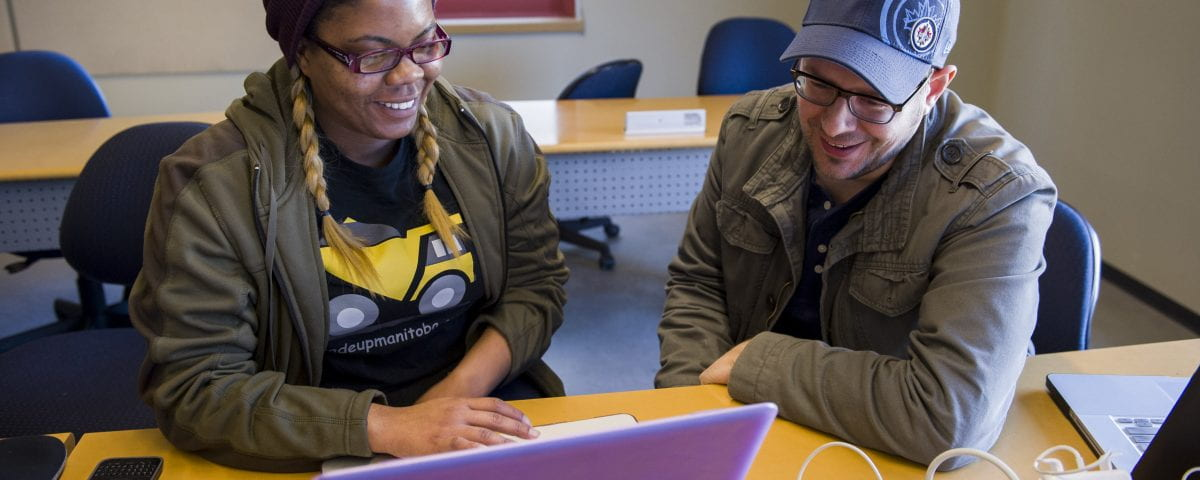 Two students are pictured looking at a laptop screen