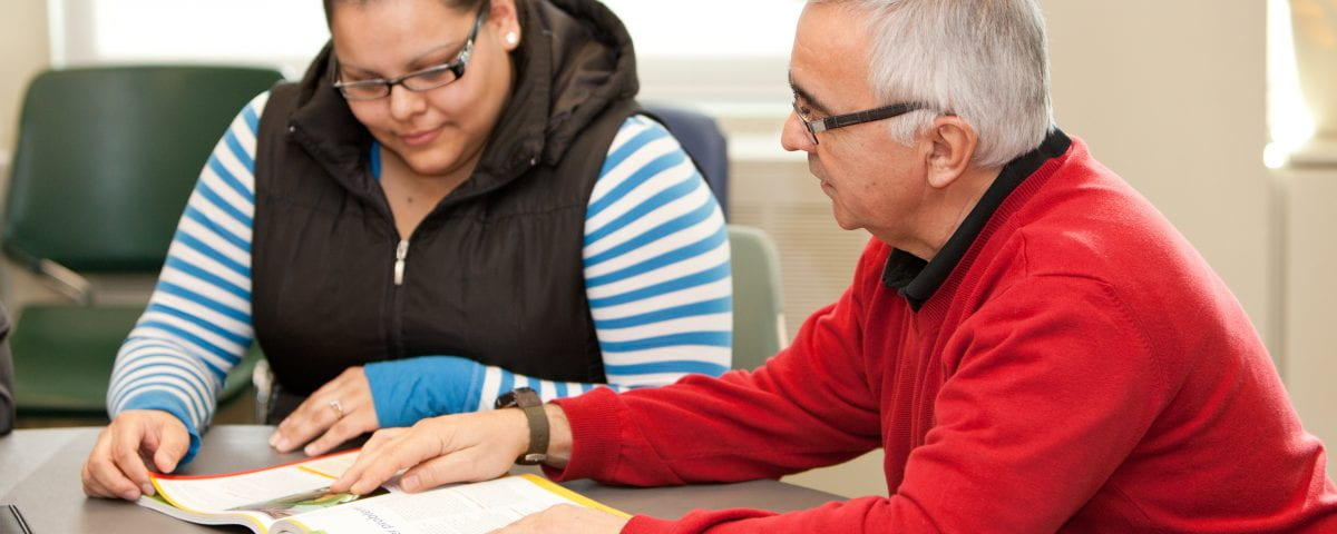 An instructor is pictured reviewing a textbook with a student