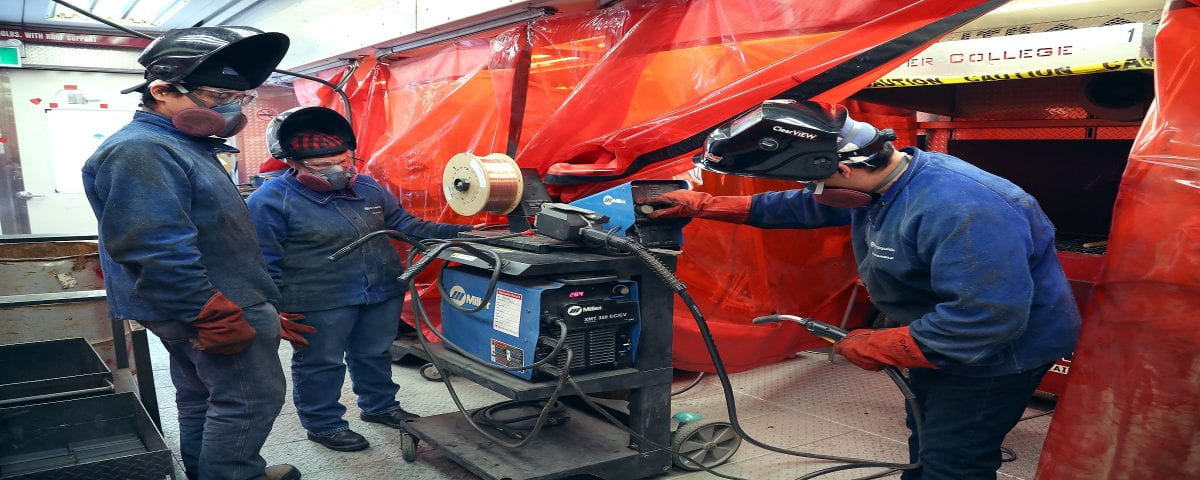 three students with welding equipment