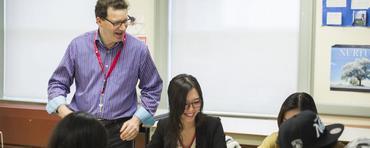 An instructor helps students in the classroom