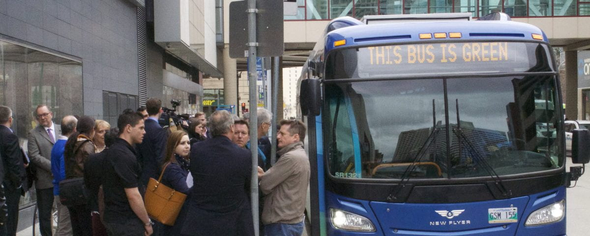 People are pictured at a bus stop